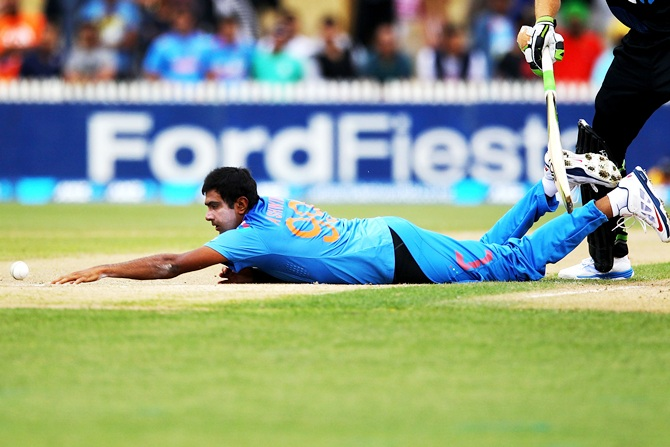 Ravichandran Ashwin of India dives for his own bowling