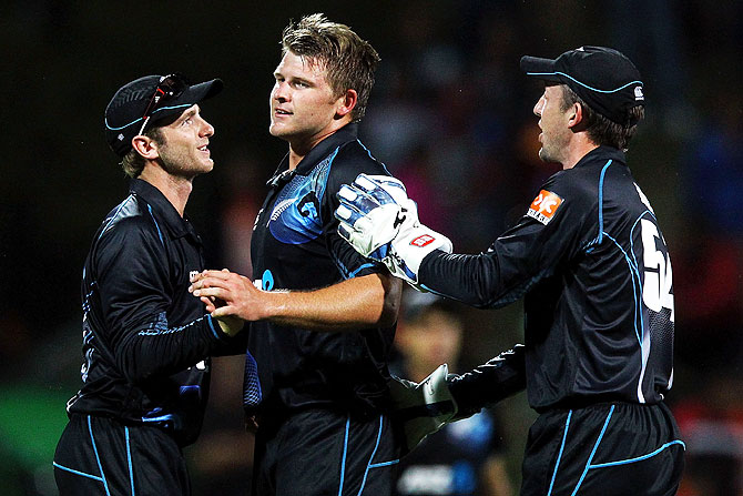 Corey Anderson of New Zealand celebrates with Kane Williamson and Luke Ronchi after dismissing Ravindra Jadeja during the One Day International in Hamilton on Wednesday