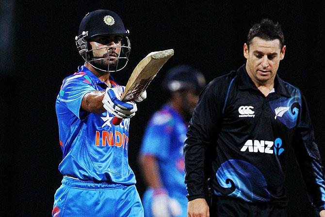 Virat Kohli of India celebrates his half century as Nathan McCullum of New Zealand looks on