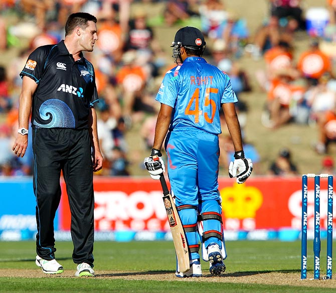 Mitchell McClenaghan (left) exchanges words with Rohit Sharma