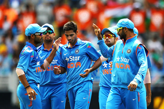 Bhuvneshwar Kumar of India celebrates with the team after taking the wicket of Jesse Ryder of New Zealand