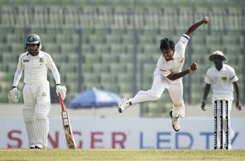 Sri Lanka's Suranga Lakmal bowls as Bangladesh's captain Mushfiqur Rahim (L) watches during the first day of the first Test in Dhaka