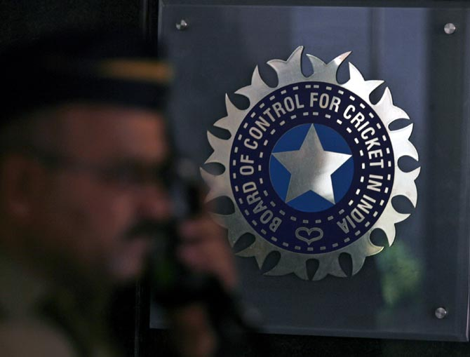 A policeman walks past a logo of the Board of Control for Cricket in India (BCCI) during a governing council meeting of the Indian Premier League (IPL) at BCCI headquarters in Mumbai
