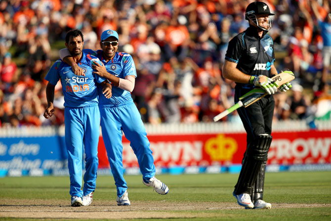 Martin Guptill of New Zealand walks off as Mohammed Shami (left) and Rohit Sharma of India celebrate his dismissal