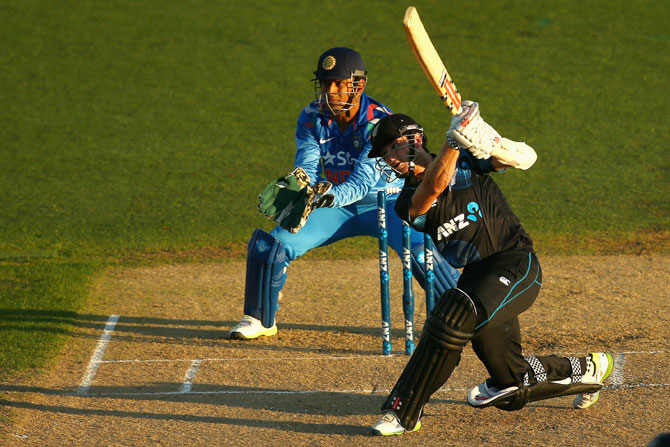Kane Williamson of New Zealand hits a shot as Dhoni looks on