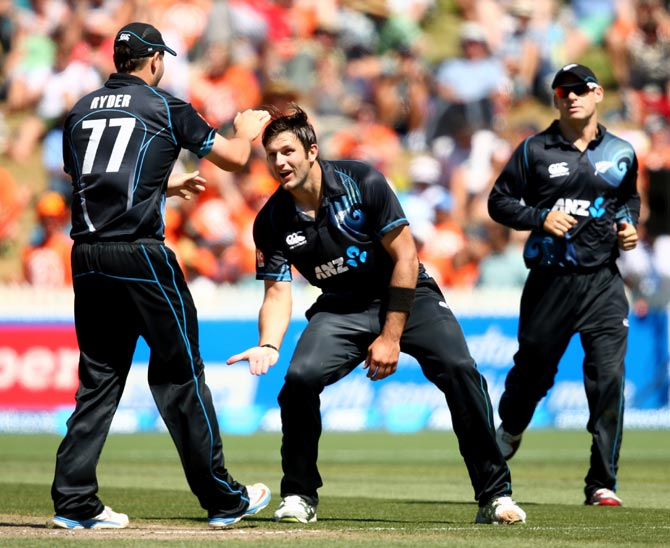 Hamish Bennett (centre) celebrates a wicket