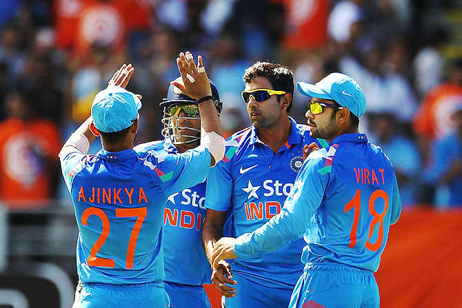 MS Dhoni of India celebrates with teammates Ravichandran Ashwin, Virat Kohli and Ajinkya Rahane after dismissing Corey Anderson of New Zealand