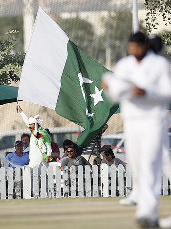 A fan waves a Pakistan flag during the final day of England's second practice match against the Pakistan Cricket Board XI at the ICC Global cricket academy ground in Dubai in January 2012