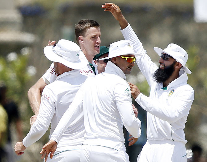 South Africa's captain Hashim Amla (R) celebrates with teammate Morne Morkel (2nd from left) after dismissing Sri Lanka's Dinesh Chandimal on Sunday