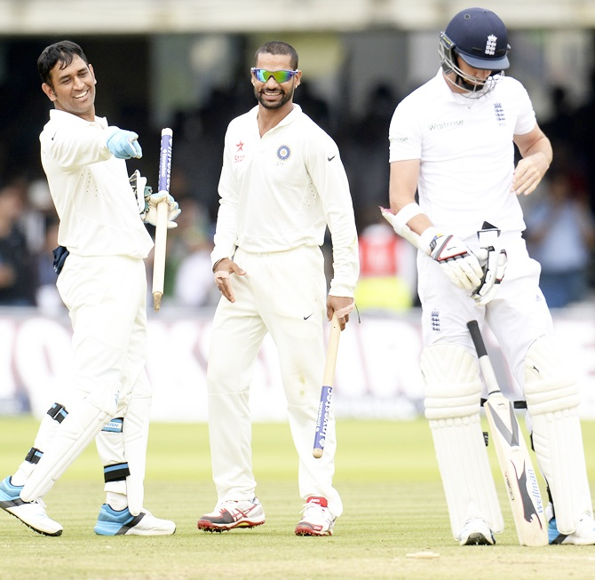 Mahendra Singh Dhoni and Shikhar Dhawan watch England's James Anderson, right, leave the field after India won the second Test at Lord's.