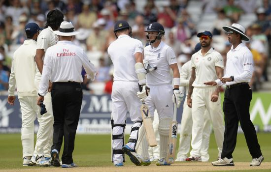 England's James Anderson (centre, left) pushes teammate Joe Root