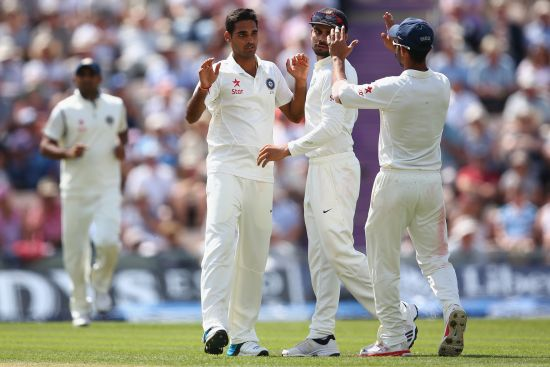 Bhuvneshwar Kumar, second left, of India celebrates taking the wicket of Joe Root of England