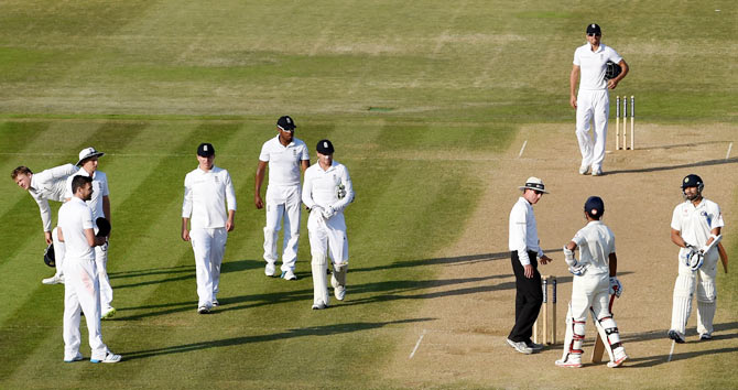 England bowler James Anderson (left) looks on as India batsman Ajinkya Rahane (2nd from right) talks to umpire Rod Tucker after play finishes on day four on Wednesday