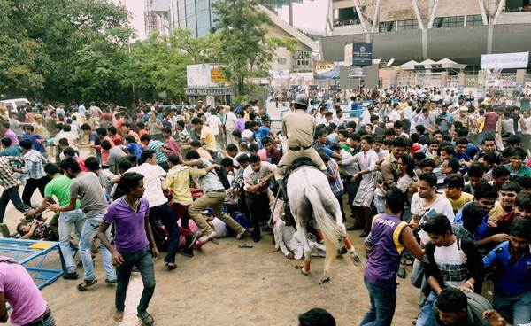 A horse-mounted policeman tries to disperse the crowd in front of the Eden Gardens, ahead of the felicitation function for IPL champions Kolkata Knight Riders, in Kolkata on Tuesday.