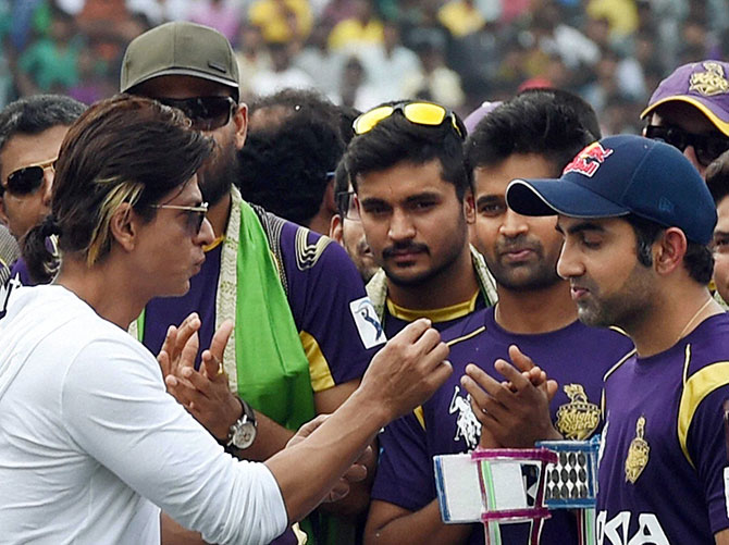 Kolkata Knight Riders owner Shahrukh Khan interacts with captain Gautam Gambhir and other players during a felicitation