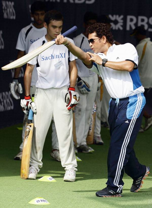 Sachin Tendulkar explains how to execute a shot during a session with young cricketers at the Singapore Cricket Club.