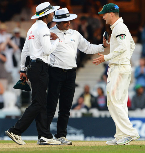 Michael Clarke of Australia talks with umpires Aleem Dar and Kumar Dharmasena as they take a light reading.