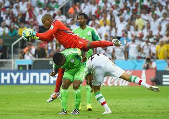 Vincent Enyeama of Nigeria makes a save over teammates Joseph Yobo and Ashkan Dejagah of Iran during the Group F World cup match at Arena da Baixada in Curitiba, Brazil.