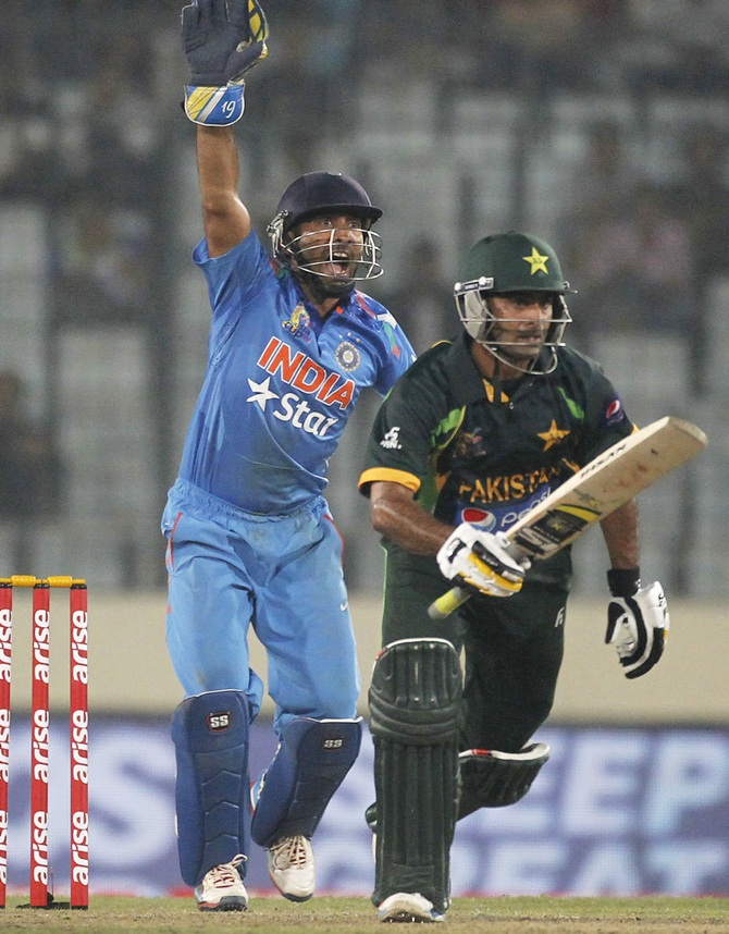 Pakistan's Mohammad Hafeez runs between the wickets as India's wicketkeeper Dinesh Karthik, left, reacts