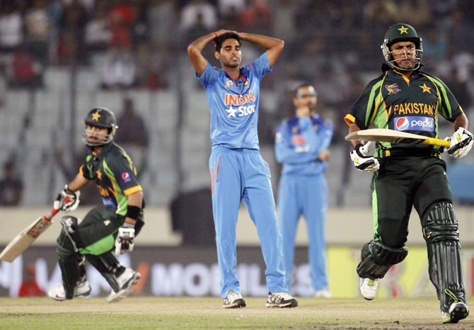Pakistan's Ahmed Shahzad,left, and Sharjeel Khan run between the wickets as India's bowler Bhuvneshwar Kumar watches.