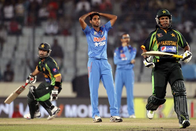 India pacer Bhuvneshwar Kumar (centre) reacts as Pakistan's Ahmed Shahzad (left) and Sharjeel Khan run between the wickets.