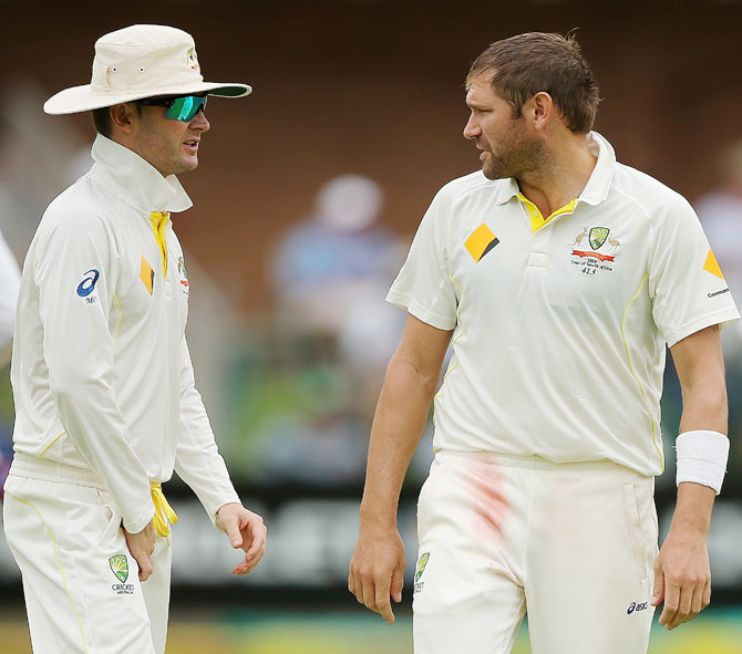 Michael Clarke of Australia speaks to his teammate Ryan Harris