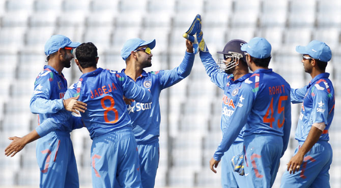 Indian players celebrate after picking a wicket