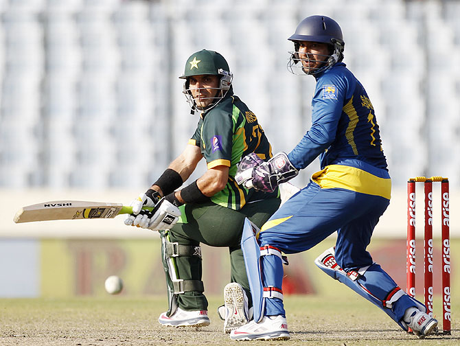 Pakistan's captain Misbah-ul-Haq plays a shot as Sri Lanka's wicketkeeper Kumar Sangakkara watches on Saturday.