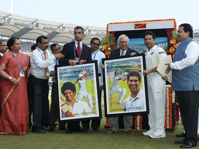 Sachin Tendulkar poses with the framed versions of the  stamp produced in his honour