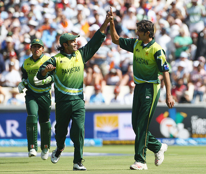 Sohail Tanveer is congratulated by his Pakistan teammates after taking the wicket of Robin Uthappa