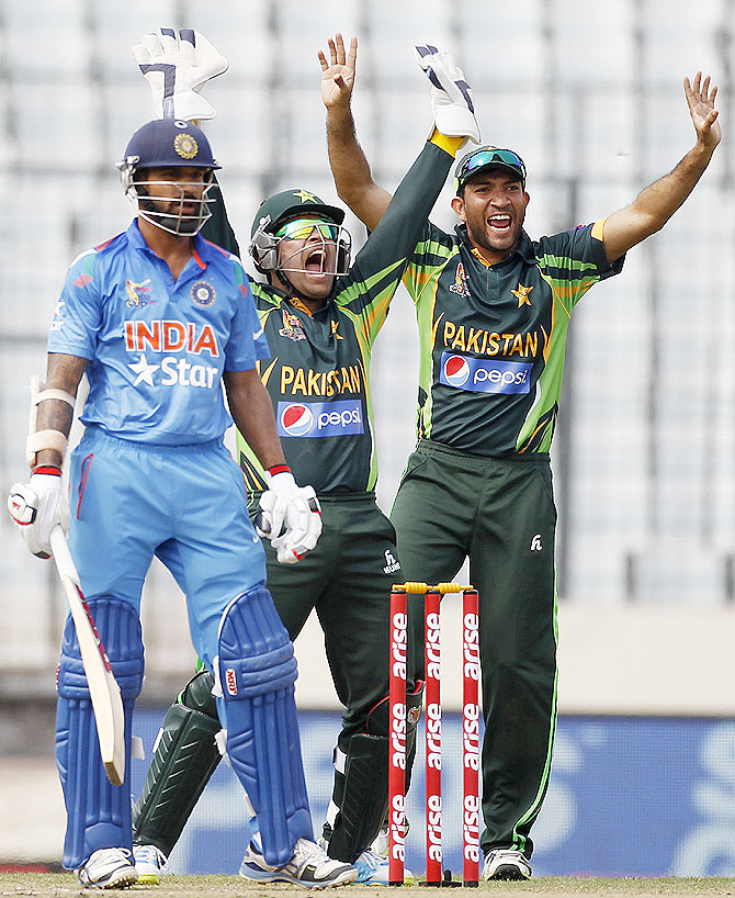 India's Shikhar Dhawan reacts on being dismissed as Pakistan's wicketkeeper Umar Akmal, centre, and Sohaib Maqsood, right, appeal