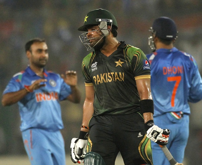 Pakistan's Umar Akmal reacts after teammate Shoaib Malik is dismissed by India's captain and wicketkeeper MS Dhoni