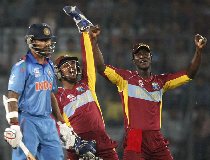 West Indies' wicketkeeper Andre Fletcher, centre, and captain   Darren Sammy,right, appeal for India's Shikhar Dhawan's dismissal successfully