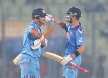 Virat Kohli and MS Dhoni of India embrace after clinching victory over Bangladesh on Friday