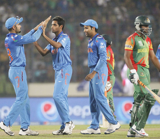 Bangladesh's Shakib Al Hasan leaves the field as India's fielders congratulate Bhuvneshwar Kumar (3rd left) on dismissing him