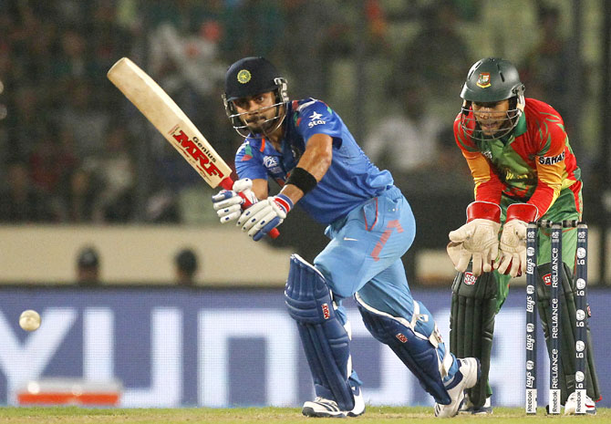 Virat Kohli plays a ball as Bangladesh's captain and wicketkeeper Mushfiqur Rahim (right) watch