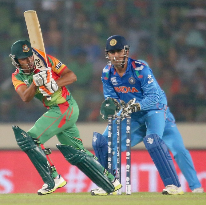 Anamul Haque of Bangladesh bats as MS Dhoni of India looks