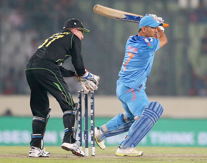 MS Dhoni of India bats as Brad Haddin of Australia looks on