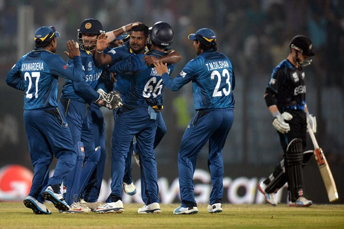 Rangana Herath (centre) celebrates with teammates after taking the wicket of Jimmy Neesham.