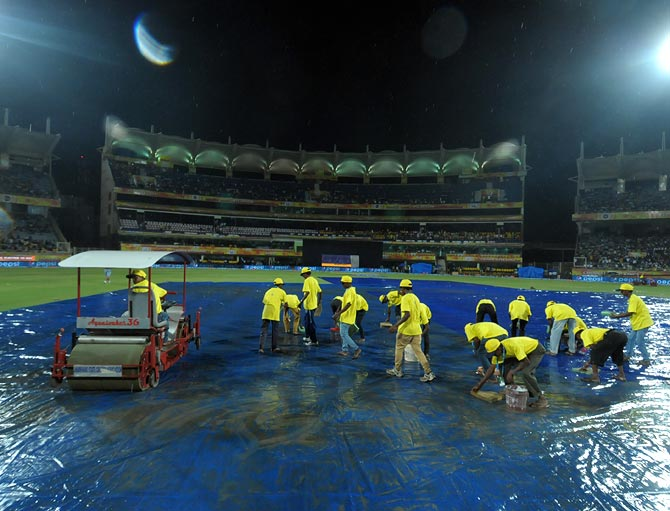 Ground staff perform mopping up operations after rain lashed the JSCA International Stadium in Ranchi