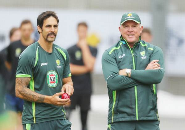 Mitchell Johnson of Australia prepares to bowl as bowling coach Craig McDermott looks on during an Australian Ashes training session at the Melbourne Cricket Ground on December 23, 2013