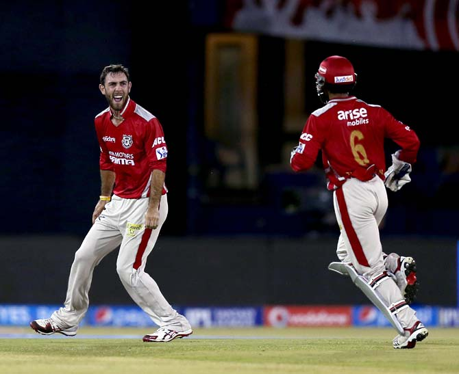 Glenn Maxwell (left) celebrates the wicket of Suresh Raina with team mate Wriddhiman Saha