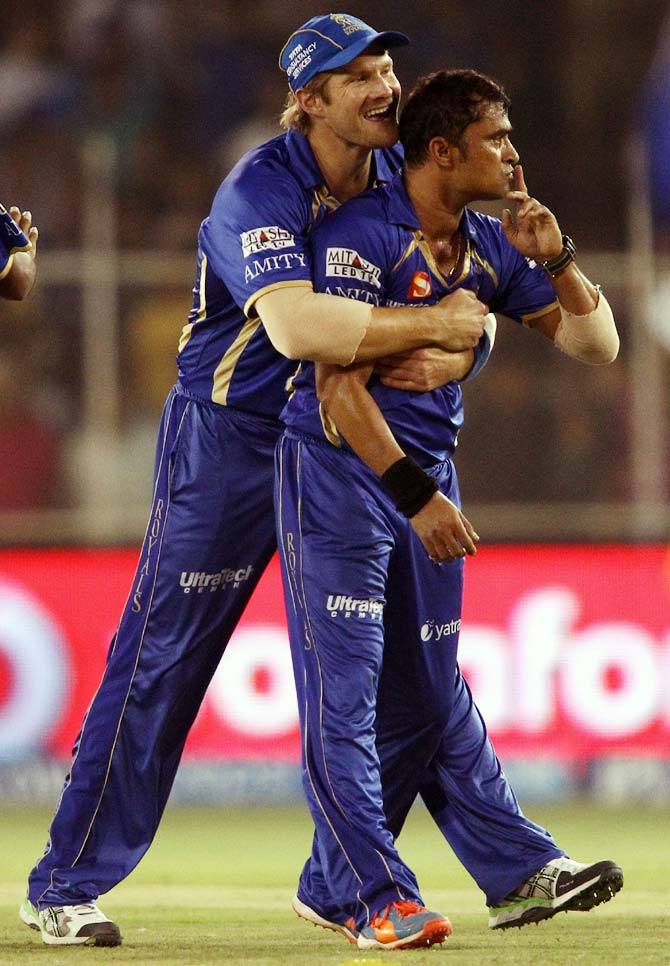 Shane Watson (left) congratulates Pravin Tambe after he dismissed David Warner