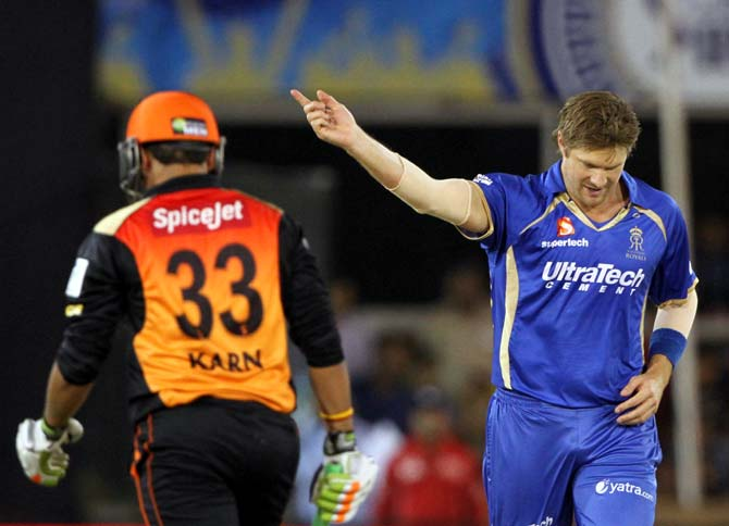 Shane Watson (right) celebrates after completing his hat-trick as Karn Sharma walks back after his dismissal