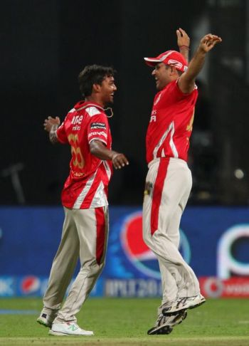 Sandeep Sharma and Virender Sehwag celebrate the fall of a wicket