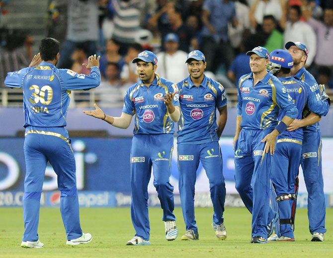 Mumbai Indians' Pragyan Ojha is congratulated by captain Rohit Sharma and teammates