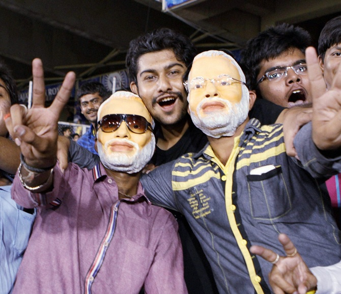 Fans wearing mask of Narendra Modi during an IPL-7 match