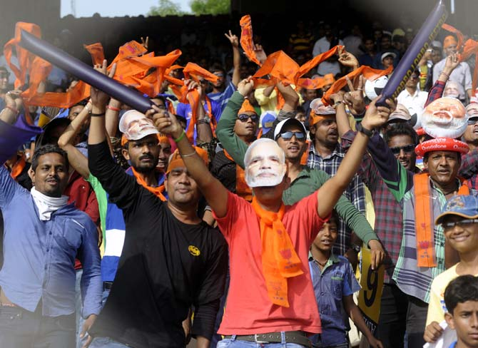 Fans wearing Narendra Modi masks at the IPL match between Rajasthan Royals and Kolkata Knight Riders in Ahmedabad.