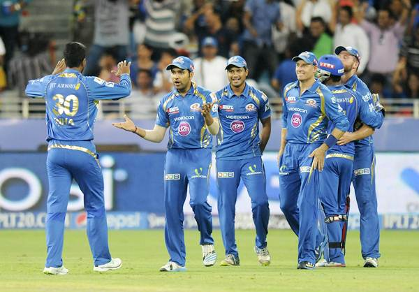Mumbai Indians players celebrate the fall of a wick
