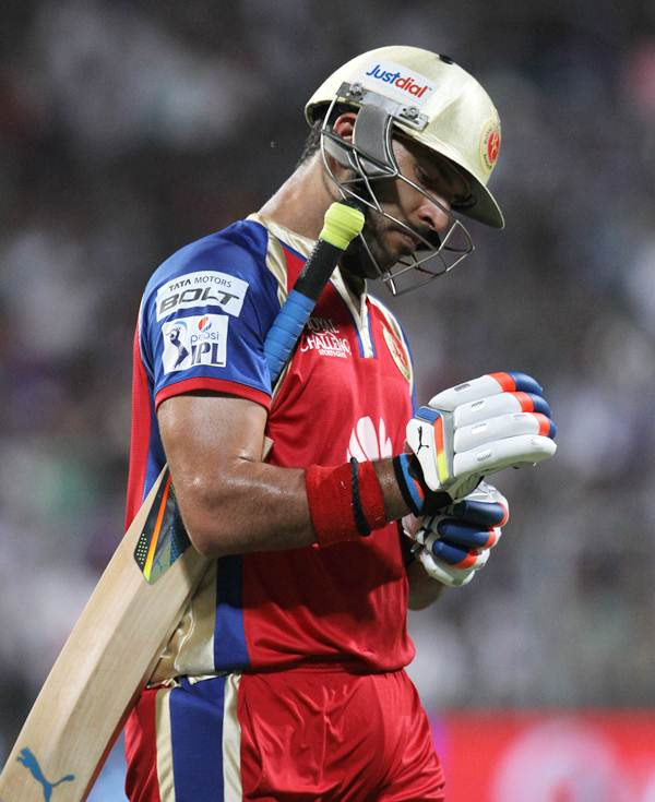 Yuvraj Singh walks back after being dismissed.